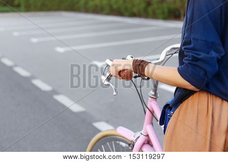 Close up view of female hand holding bicycle handlebar