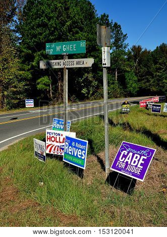 Pittsboro NC - October 23 2016: A jumble of campaign advertising signs for both local and national candidates at the intersection of two rural roads