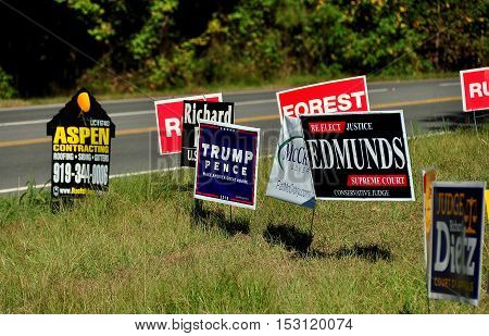 Pittsboro NC - October 23 2016: Campaign 2016 political advertising signs for both local and national candidates at the intersection of two rural roads