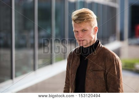 Young handsome stylish man in brown jacket in autumn time outdoor in casual style.