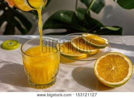 Orange juice is poured from a bottle into a glass the cut orange on a saucer.