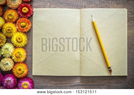 Opened blank page kraft paper notebook on wood table with pencil and straw flowers