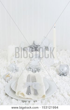christmas white table setting with candles and snow