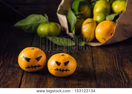 Two scary tangerines for Halloween and bunch of tangerines on background