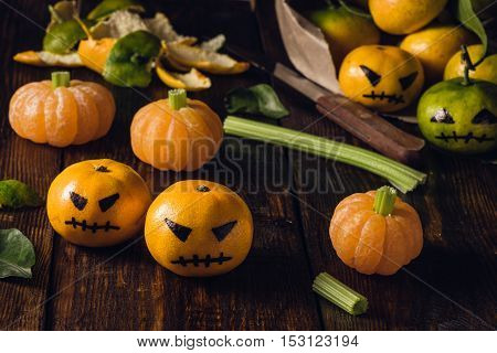 Halloween with fake pumpkins and tangerines with painted scary faces