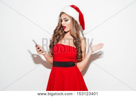 Portrait of a surprised young brunette woman in red christmas outfit looking at mobile phone isolated on the white background