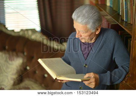 Portrait of elderly happy man with book over bookshelves