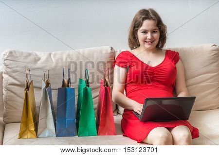 Shopping Concept. Young Pretty Woman Is Sitting On Sofa And Shop