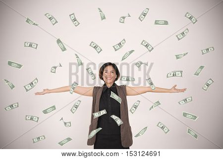 happy woman celebrates success under a money rain falling dollar bills banknotes on wall background