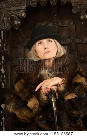 Mature woman in fur over dark background