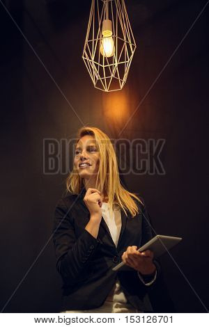 Attractive woman holding a tablet in an office.