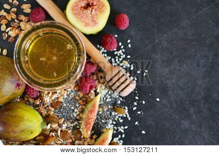 Morning breakfast - granola honey berries and fruits. Black concrete food background. Top view .
