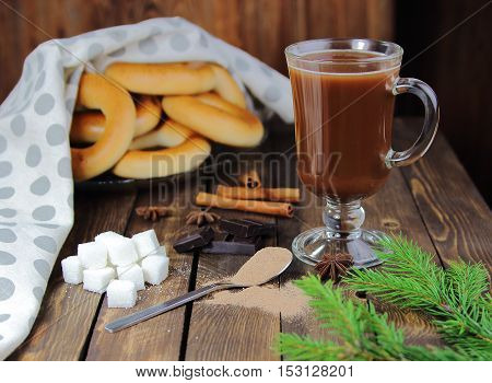 cocoa powder and hot chocolate with a fir-tree branch and bagels