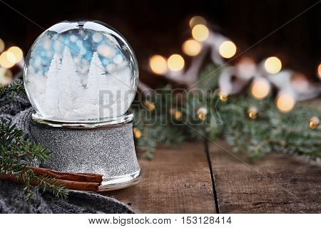 Rustic image of a snow globe surrounded by pine branches cinnamon sticks and a warm gray scarf. Shallow depth of field with selective focus on snowglobe.