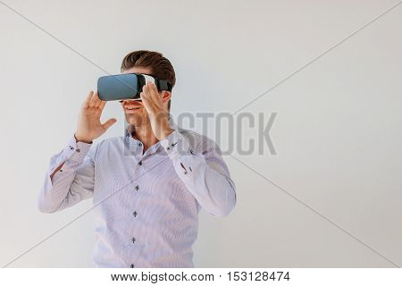 Shot of young man in virtual reality headset looking at the objects. Businessman with virtual reality goggles against grey background.