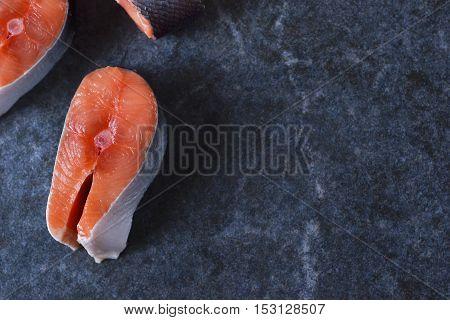 Fresh raw salmon steak on black marble background
