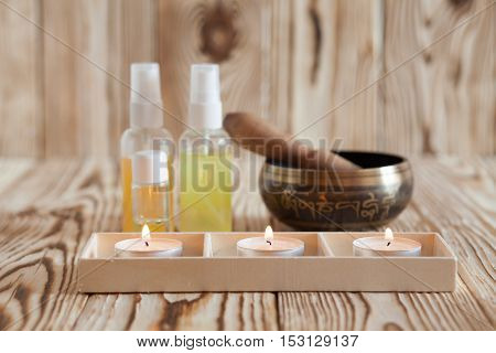 Singing bowl on wooden background. Burning candles and oil for aromatherapy and massage
