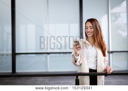 Businesswoman smiling and using phone at the offices