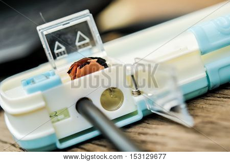 Pencil in sharpener shavings on wooden table