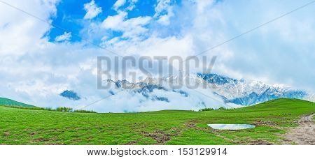 The low clouds hides the rocky snowbound mountains and fill the Stepantsminda valley Kazbegi Georgia.