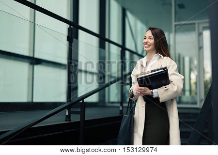 Beautiful young cute businesswoman outdoors holding files