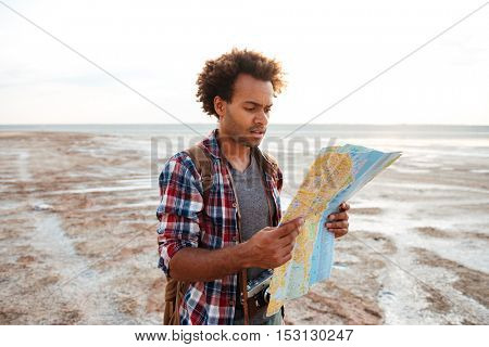 Concentrated african american young man standing outdoors and exploring map