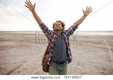 Happy attractive african young man with raised hands standing on the beach