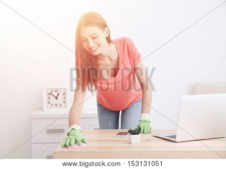 Smiling young woman cleaning table at office