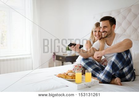 Couple relaxing in pajamas and watching tv in bed