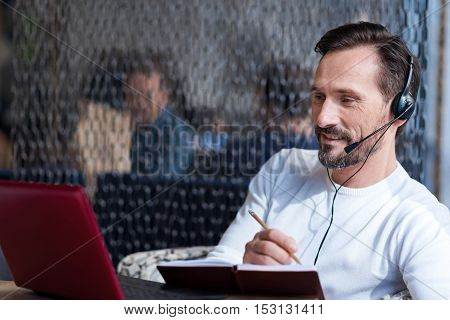 Fully involved. Portrait of middle aged bearded man sitting at table looking at laptop and taking notes.