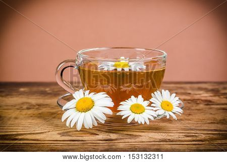 Cup of herbal tea with chamomile flowers on rustic wooden table