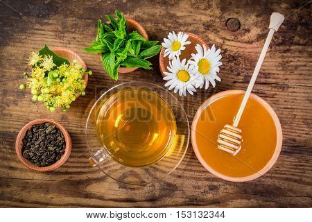 Green tea with mint, chamomile, jasmine flowers and honey on old rustic table, above view