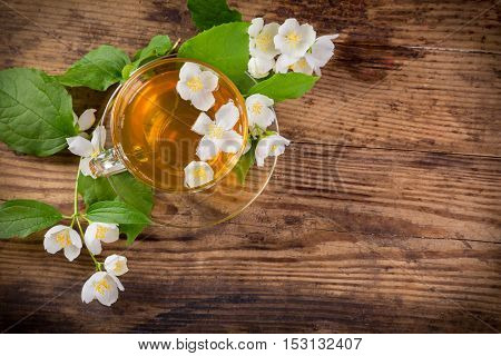 Herbal tea with jasmine flowers on rustic wooden table, above view, space for text