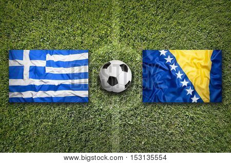 Greece vs. Bosnia and Herzegovina flags on green soccer field, 3d rendering