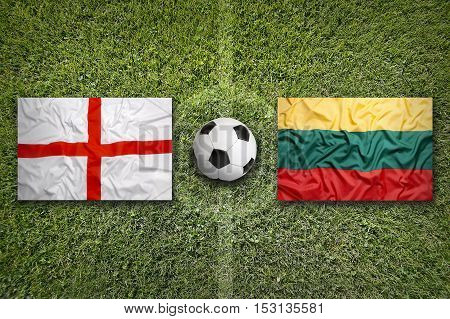United Kingdom vs. Lithuania flags on green soccer field, 3d rendering