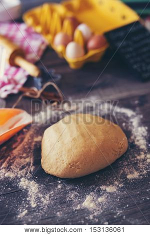 Dough ready for Christmas cookies on wooden background