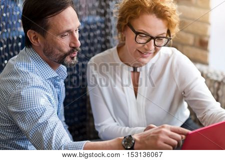 Serious dispute. Handsome bearded man pointing at laptop while discussing important thing with smiling ginger woman.
