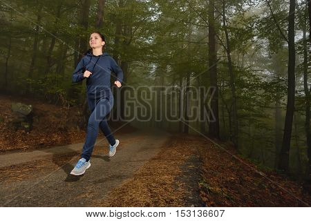 Woman running in forest area training and exercising for trail run marathon endurance. Fitness healthy lifestyle concept.
