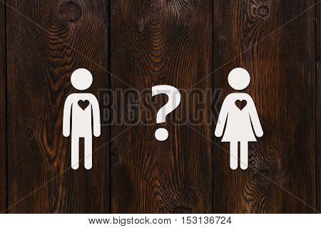 Paper man, woman and question sign on dark wooden background. Love relation concept. Abstract conceptual image