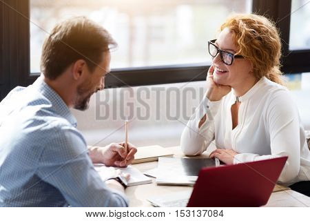 Pleasant work. Middle-aged man and woman sitting at table against big window, looking at each other and taking notes.