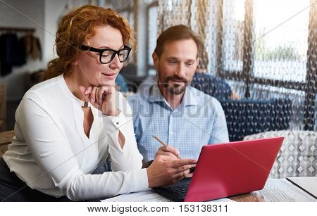 Concentrated on purpose. Ginger woman pointing at laptop near bearded man making notes while sitting in modern light office.