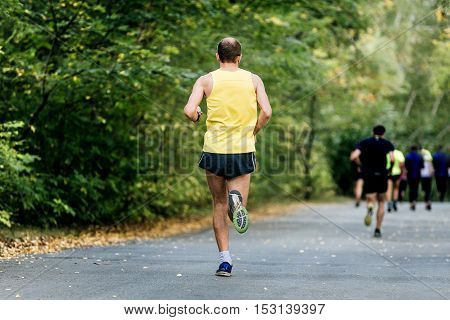 male athlete middle age running in autumn Park athletic race