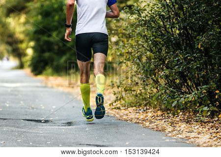 young male athlete running in autumn forest marathon. legs compression socks