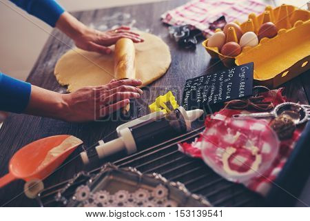 Woman make ginger bread for Christmas on wooden background