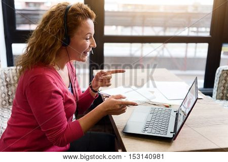 You are right. Cheerful ginger woman sitting near window, pointing with both index fingers at screen while talking per laptop.