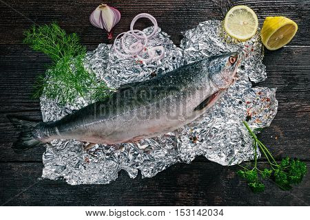 Fresh whole salmon fish on foil sheet with veggies and spices. Flat lay