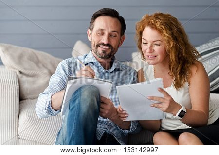 Comparing ideas. Pretty ginger woman leaning to her male partner holding notebook and pencil to get more information.