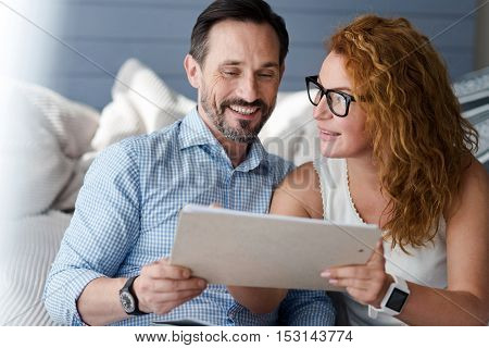 Common idea. Smiling bearded and ginger woman with glasses holding notebook together while having important conversation.