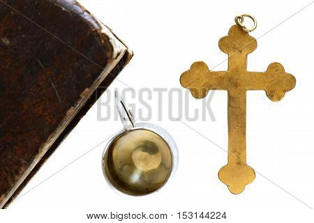 Closeup of religious objects isolated on white background: holy Bible silver chalice and golden cross