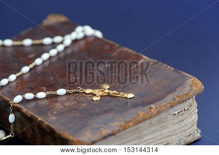 Closeup of an old golden cross necklace on an ancient book (Holy Bible)